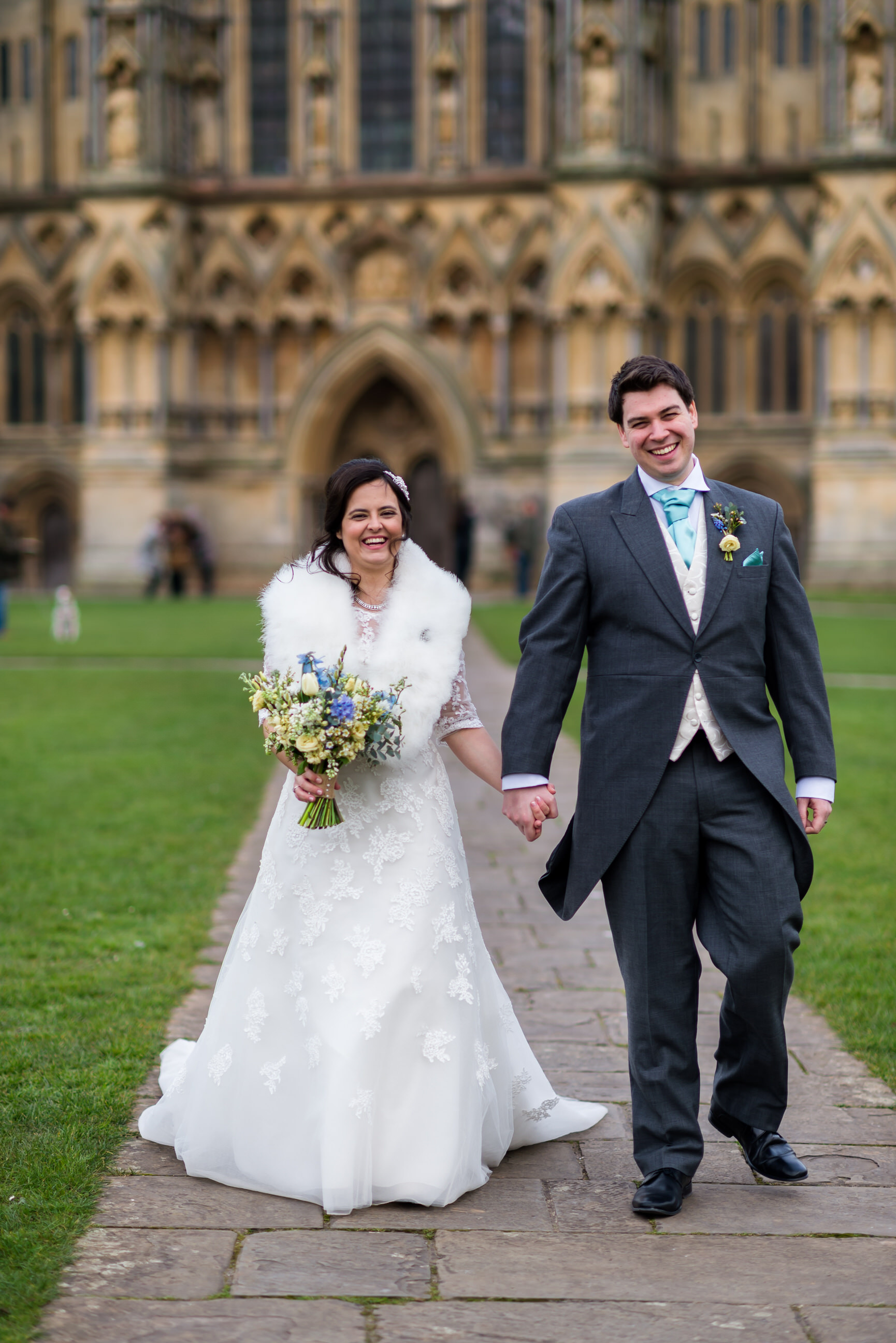 Bride and groom walking by Wells Cathedral