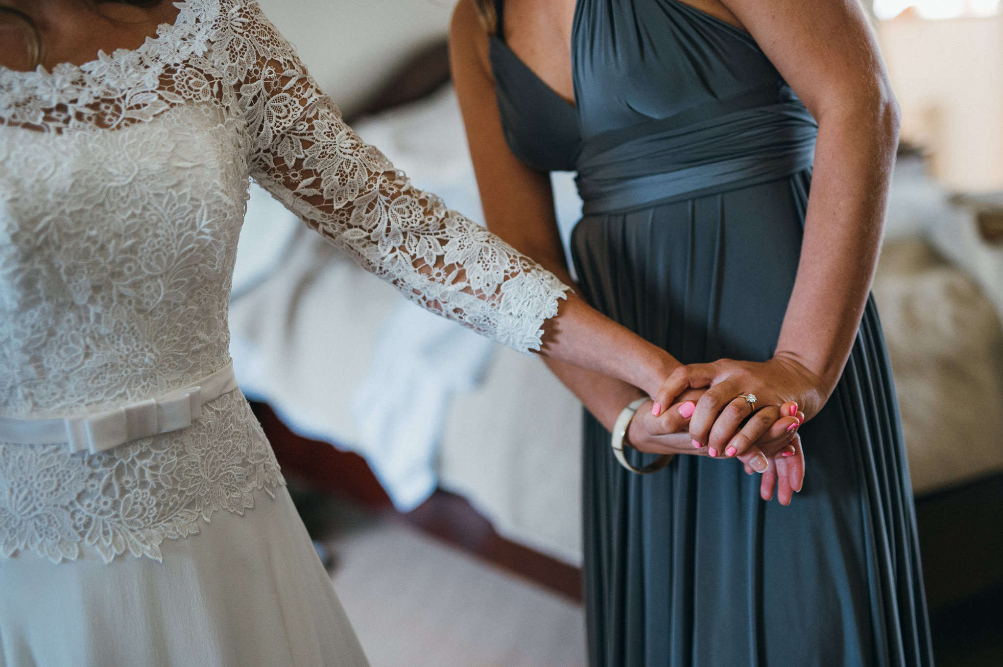 Bride holds hands with bridesmaid