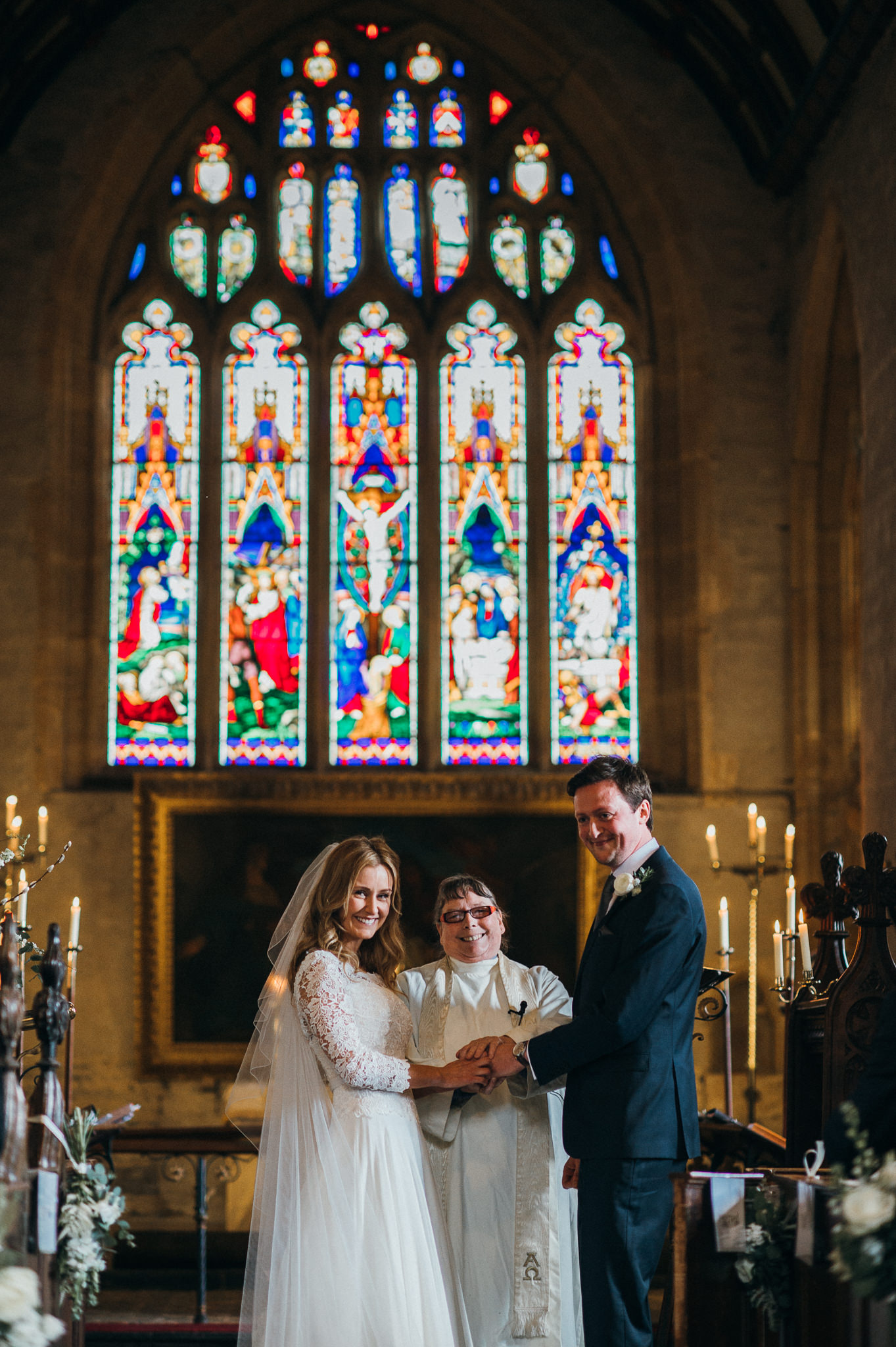 Bride and Groom exchange rings during wedding service at Church of St Peter and St Paul, Muchelney