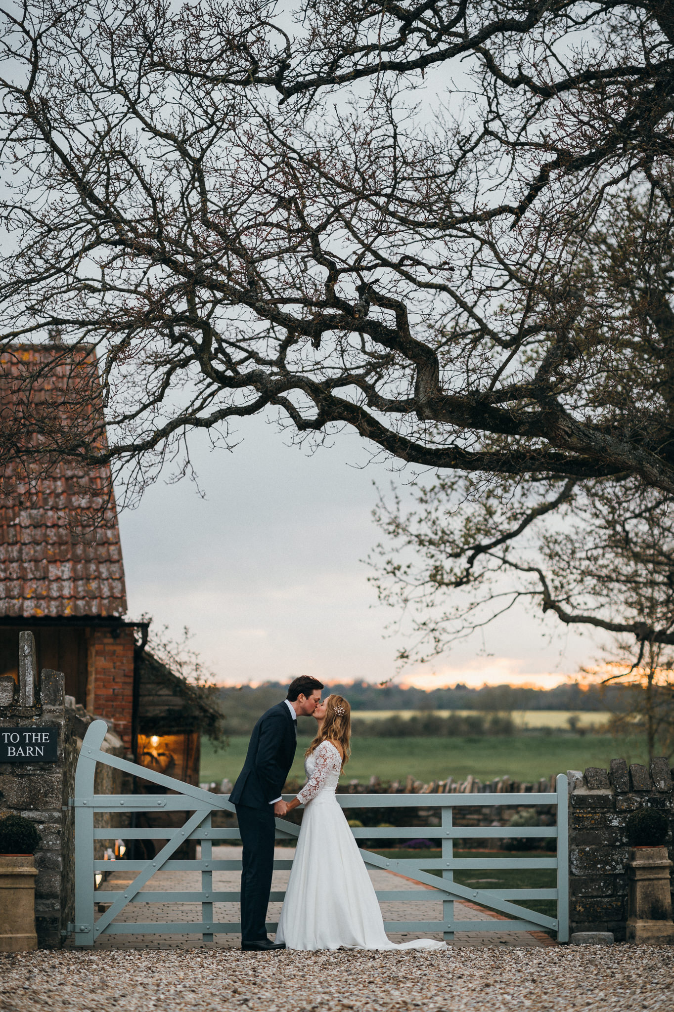 bride and groom kiss evening light almonry barn