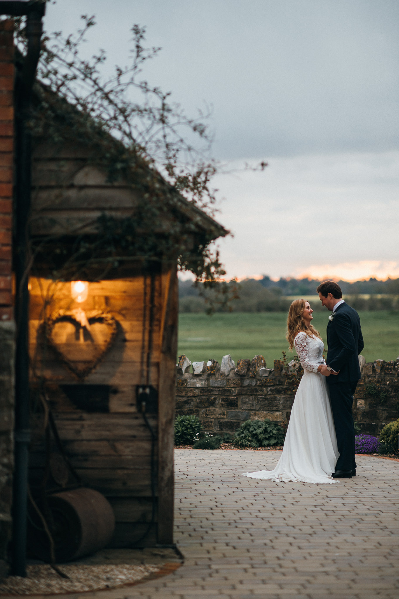 bride and groom embrace evening light almonry barn