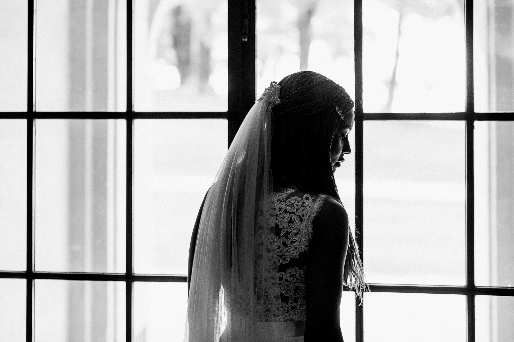 Bride backlit in Coombe Lodge window
