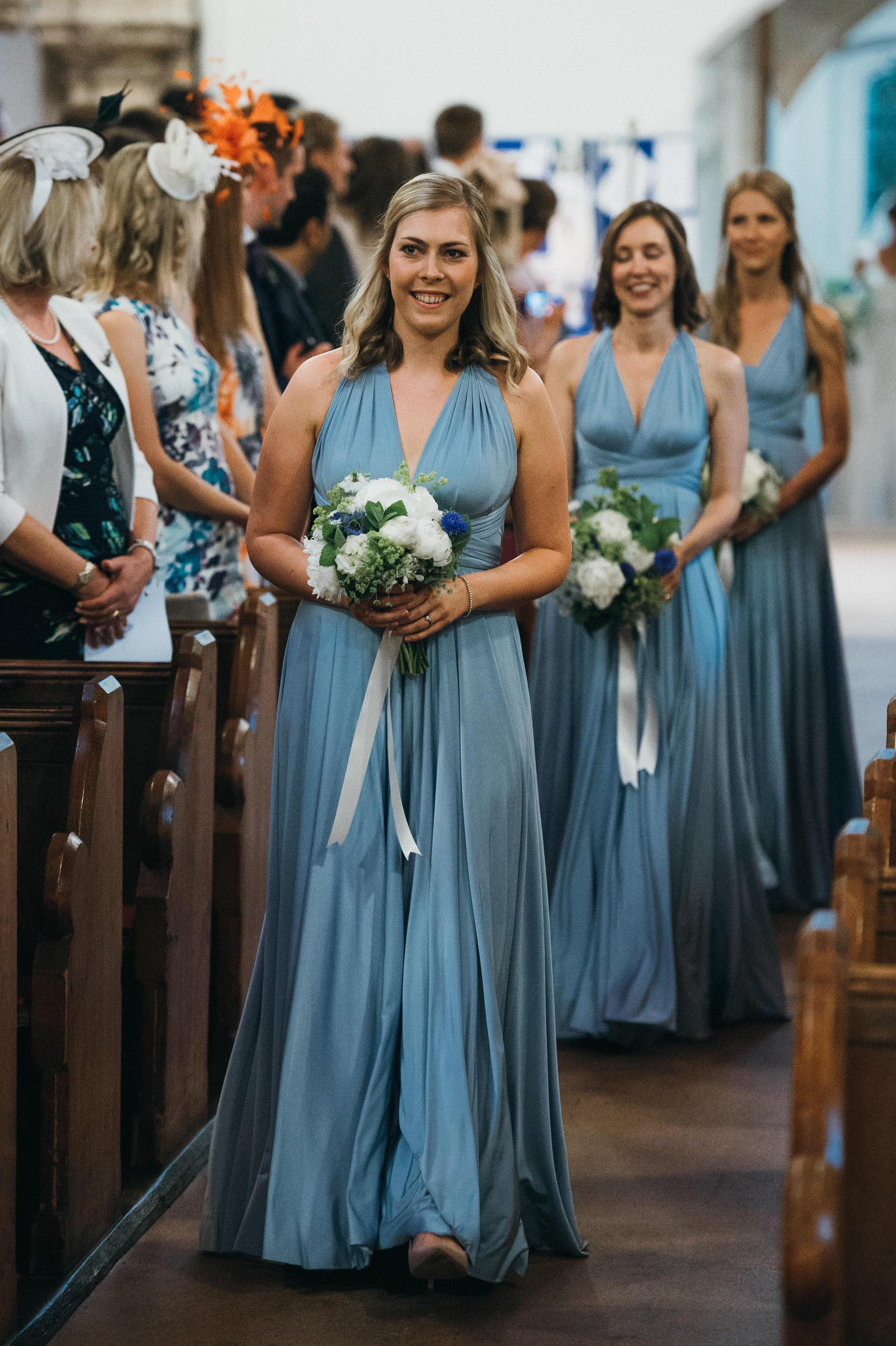 Bridesmaids walk down aisle