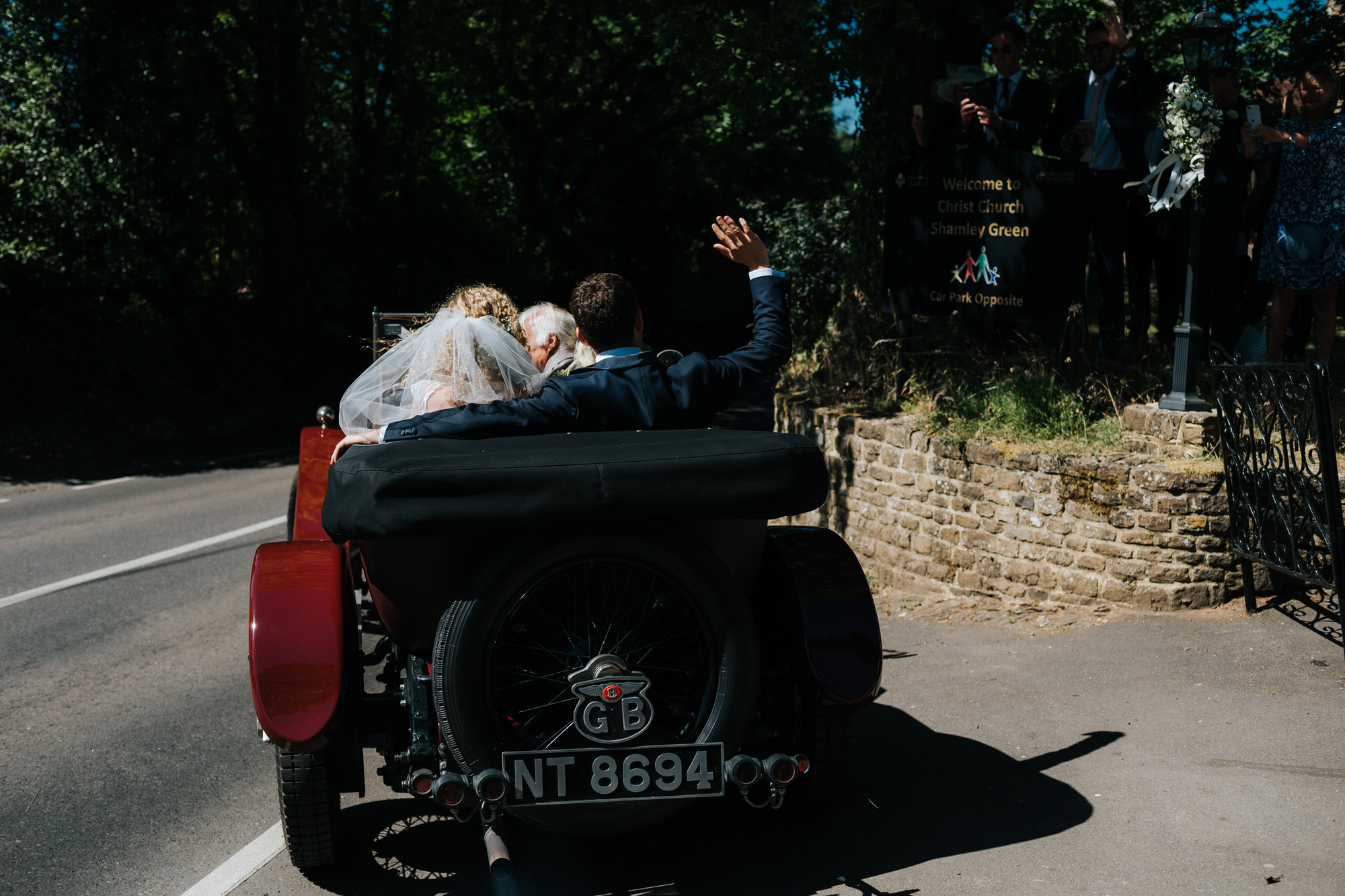 Bride and Groom drive off in open top car after getting married