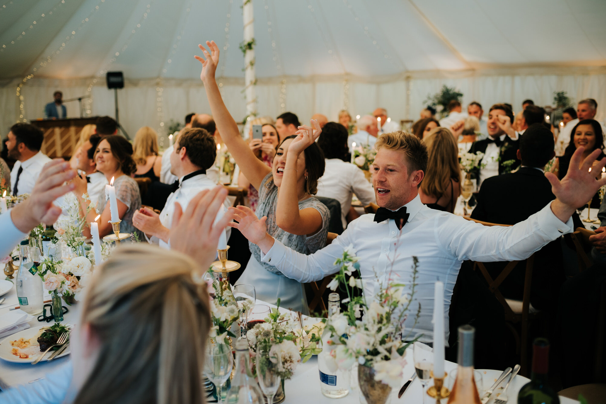 Guests sing along to music at wedding