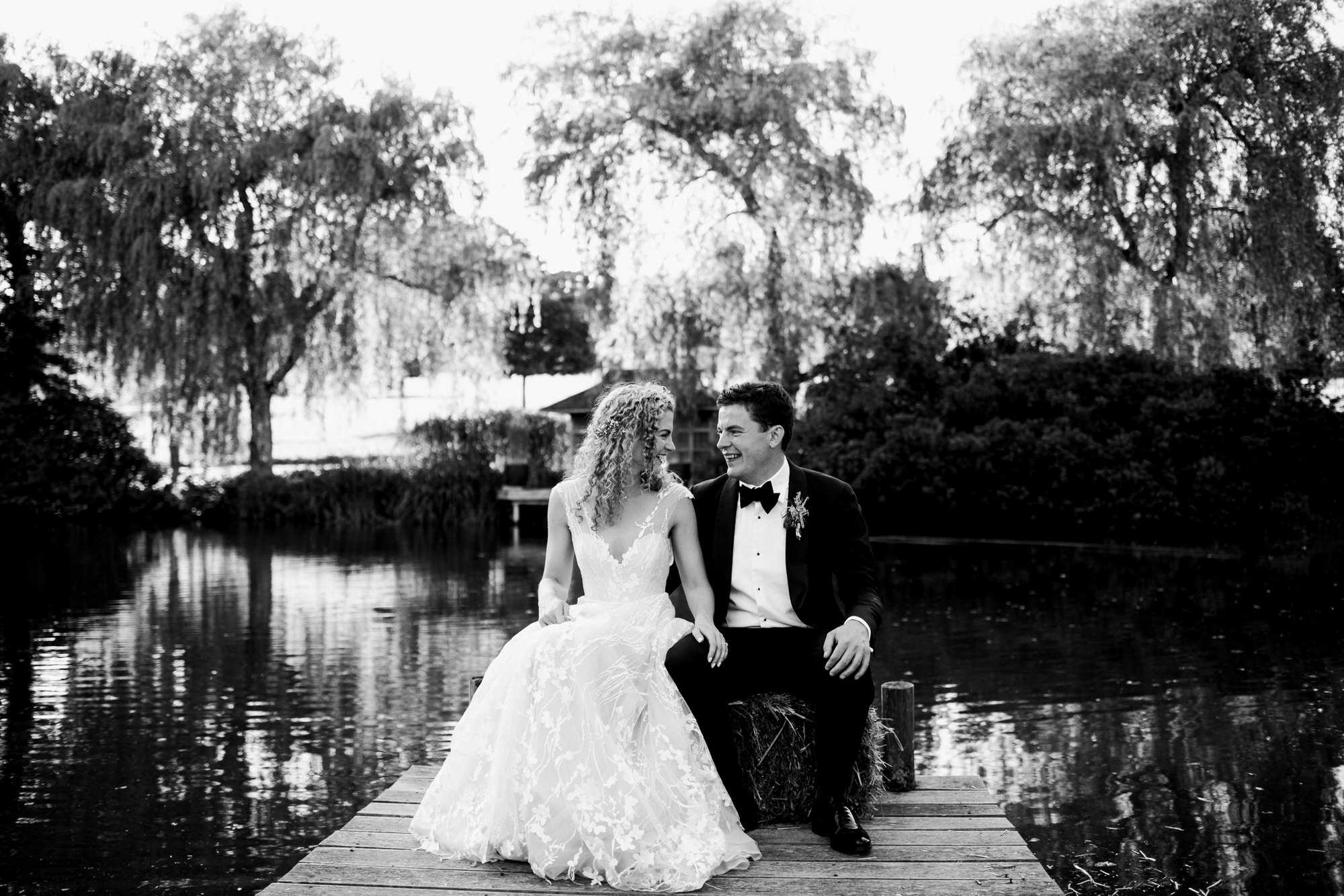 Bride and groom on jetty laughing