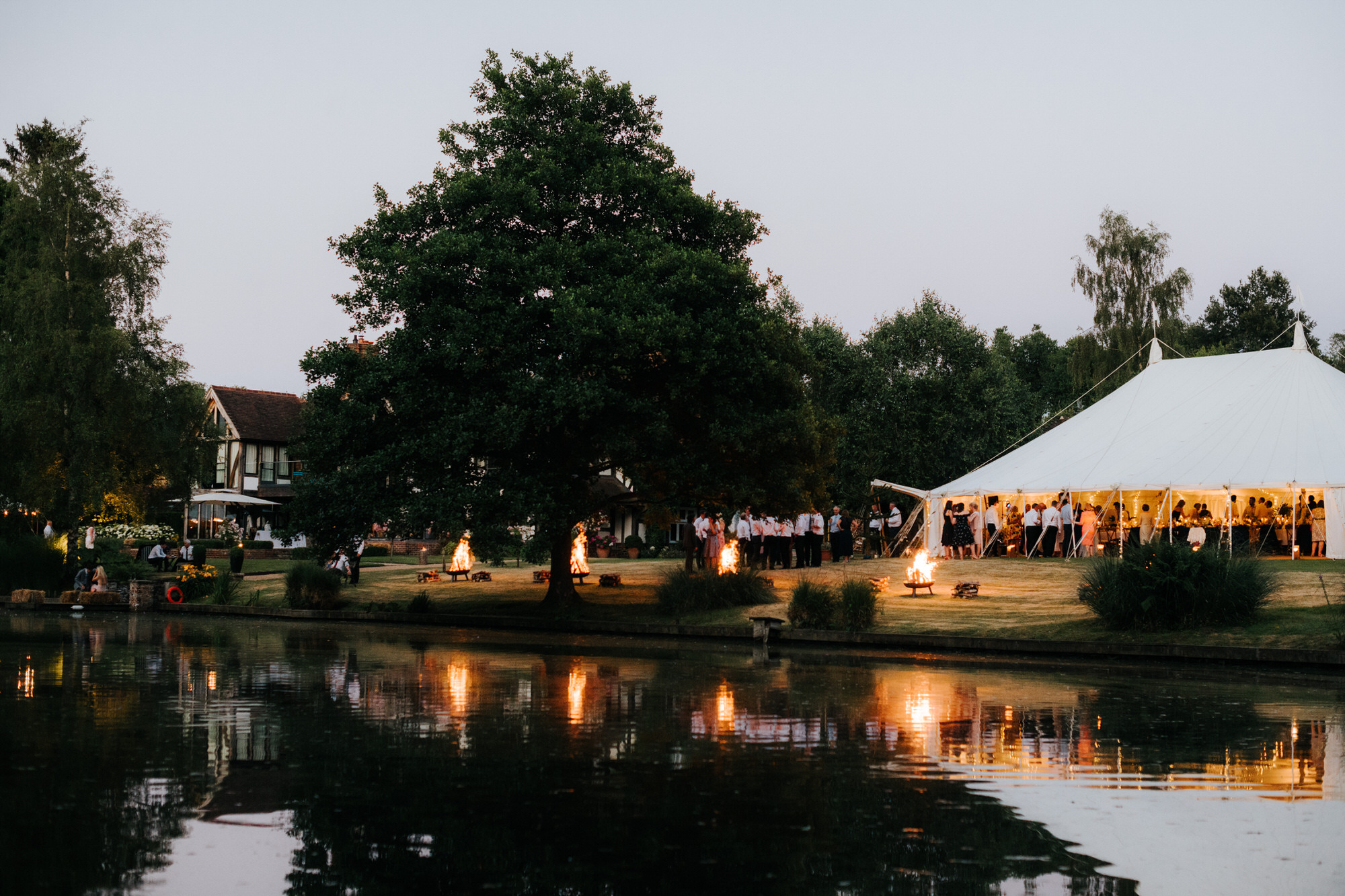 Beautiful marquee in the evening by lake side and fire pits