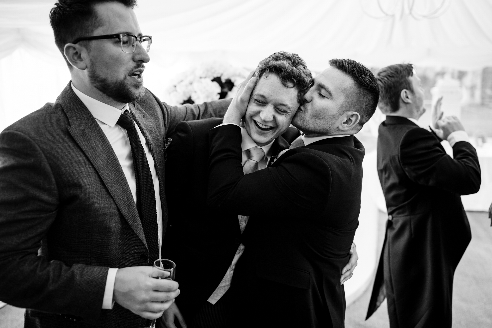 Groom gets a kiss from friend
