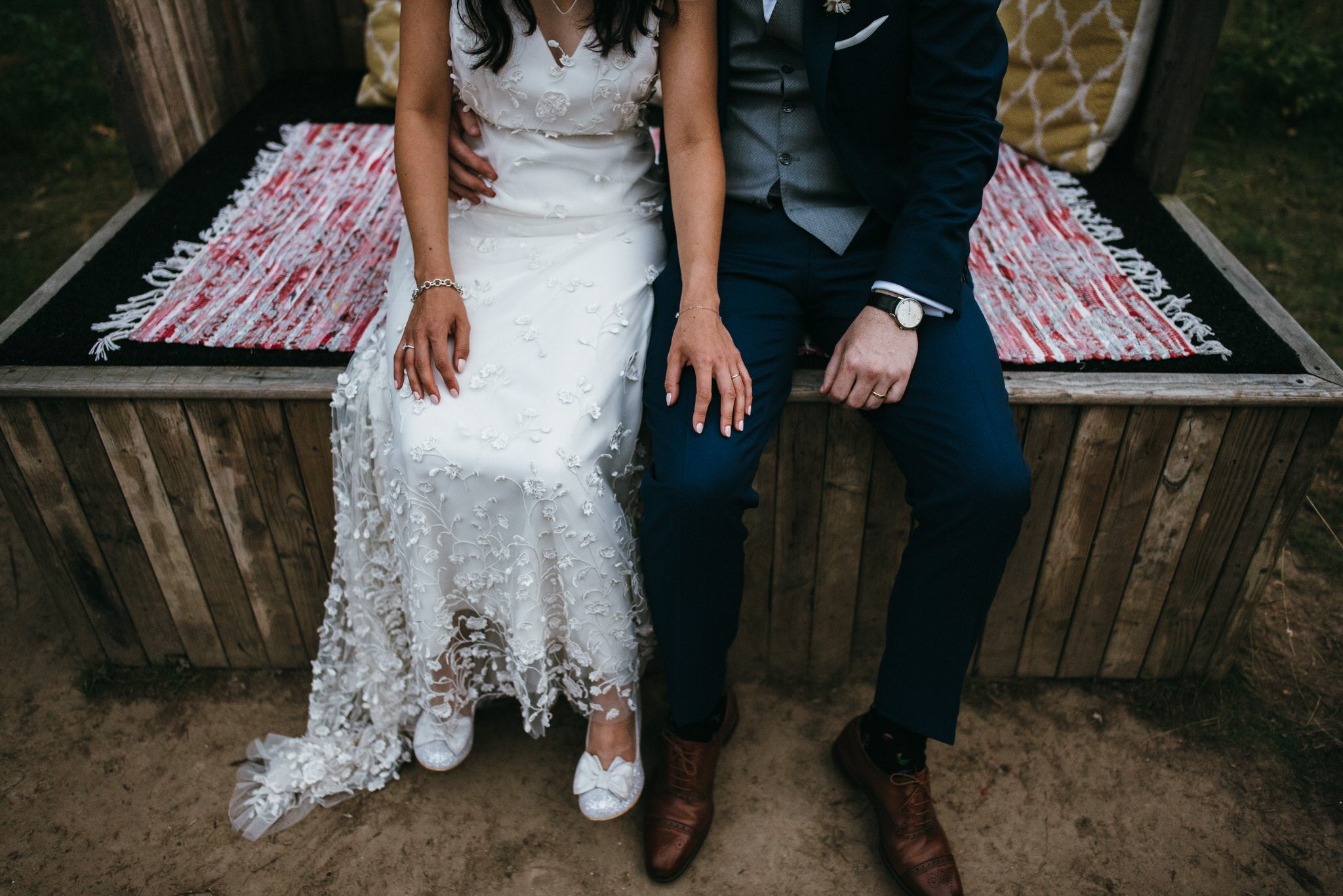 The dreys kent wedding photography - bride and groom hold hands sitting down