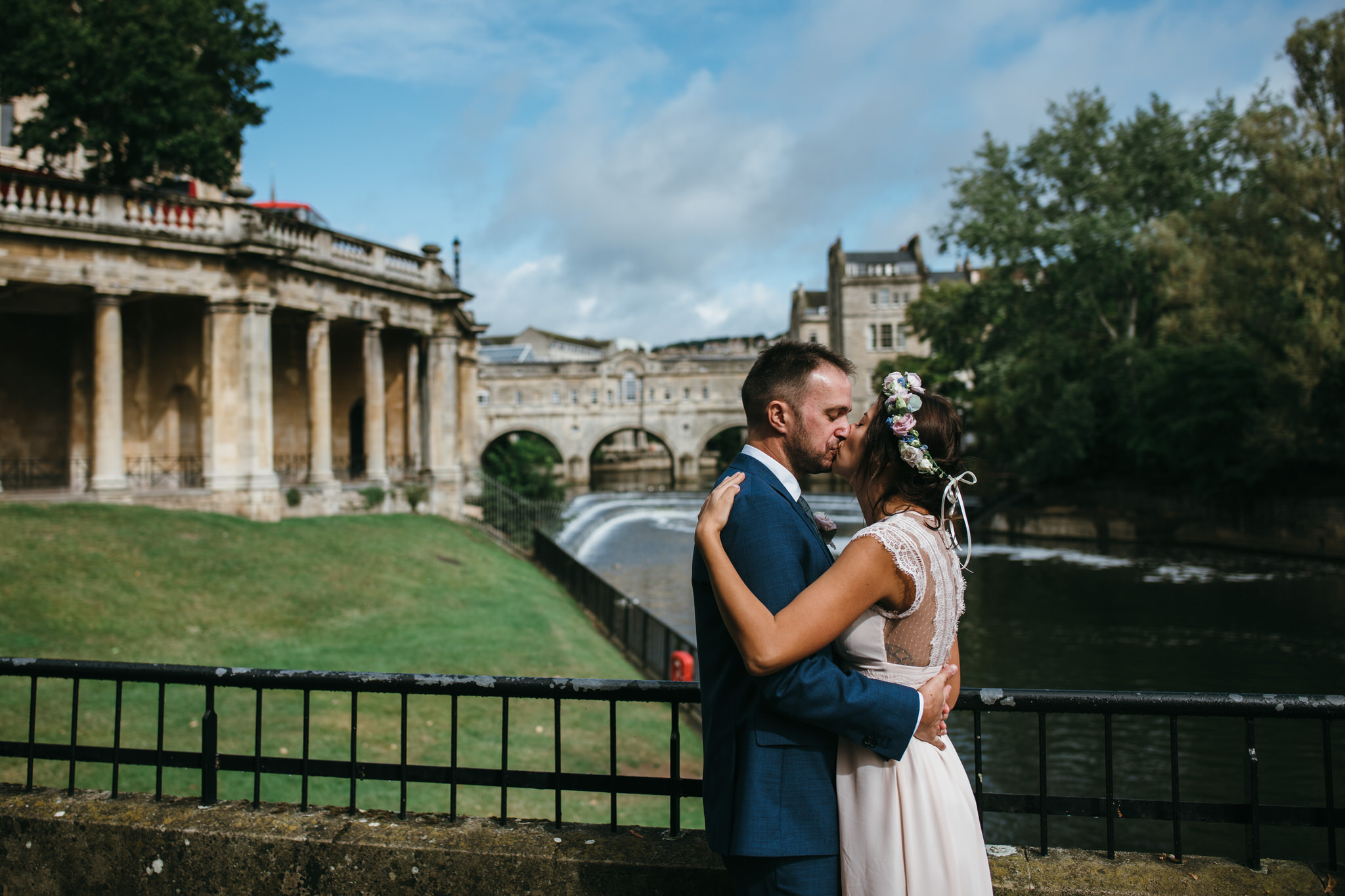 Bride and groom kiss with Pulteney bridge in background, Bath