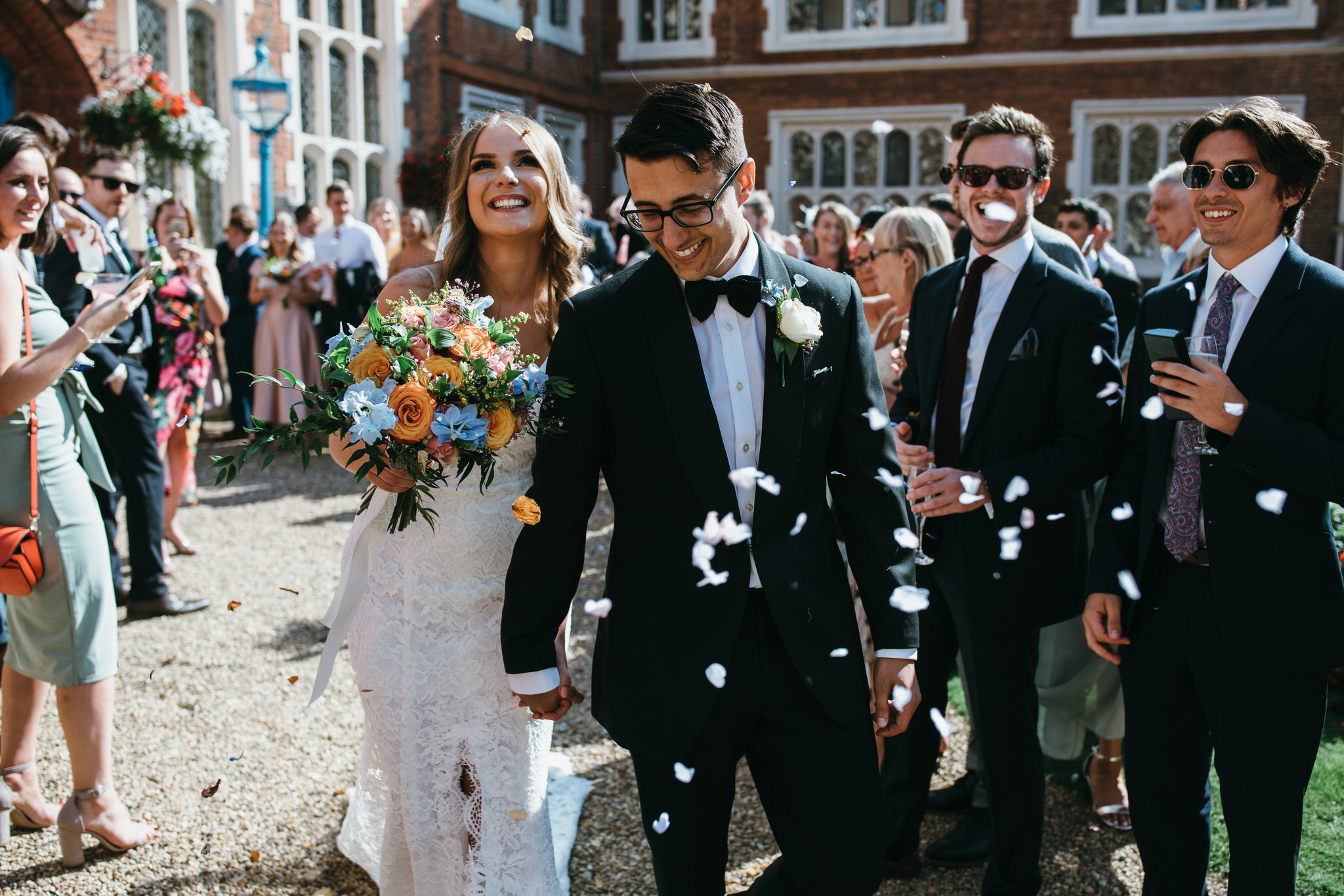 Bride and groom walk through confetti at Gosfield Hall