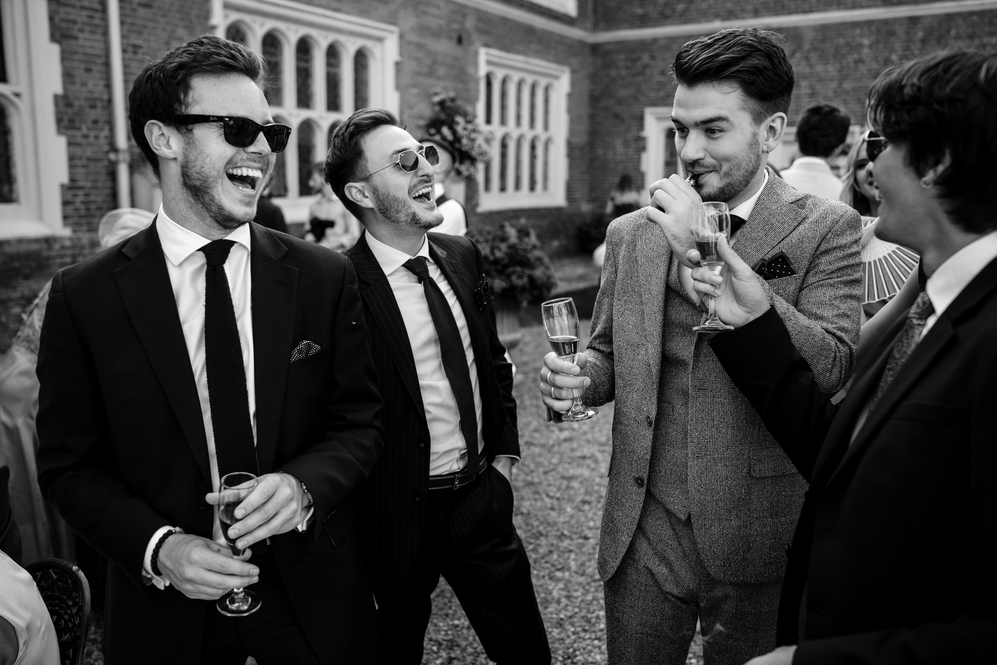 Guests laugh at Gosfield Hall wedding