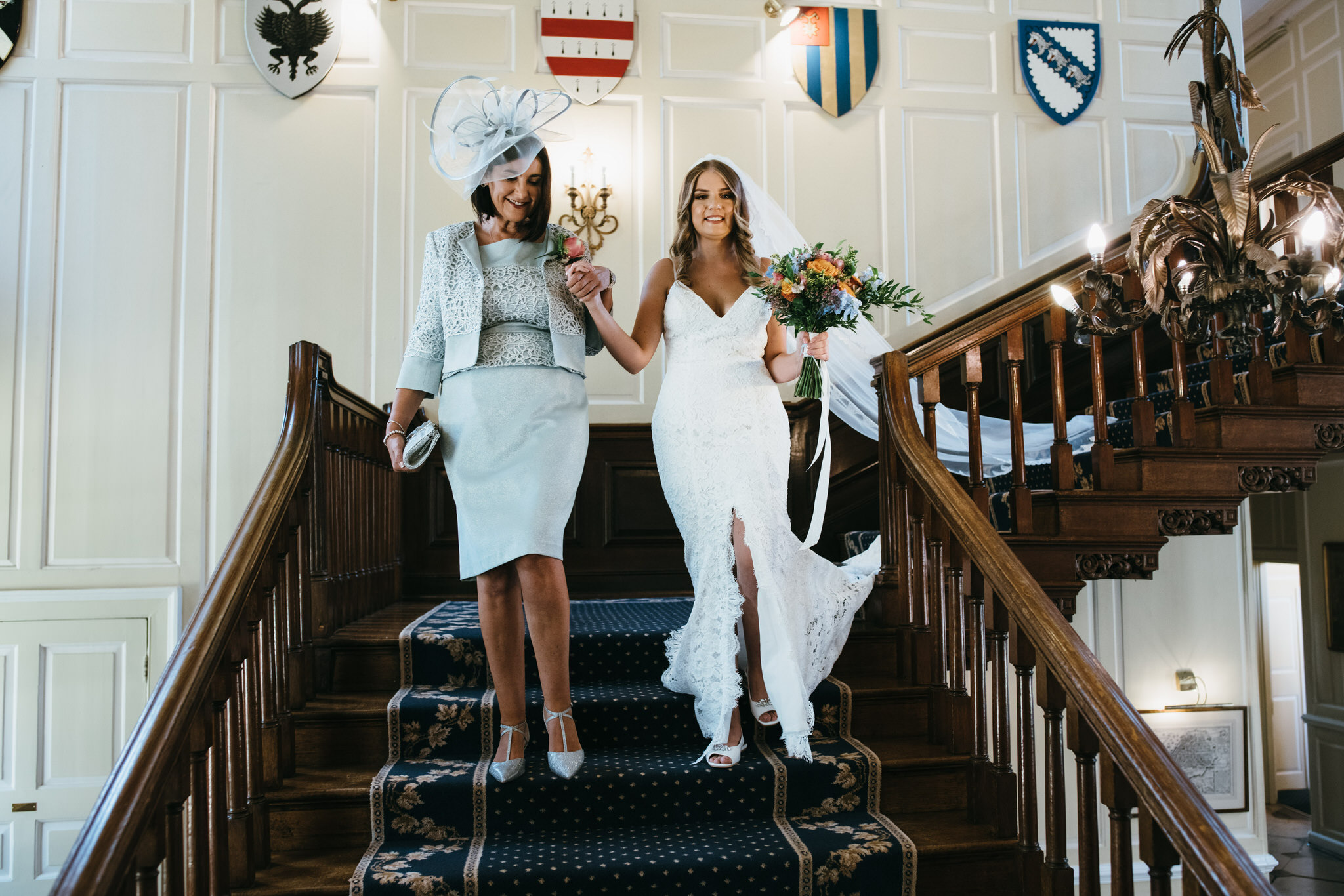 Bride walks down staircase at Gosfield hall