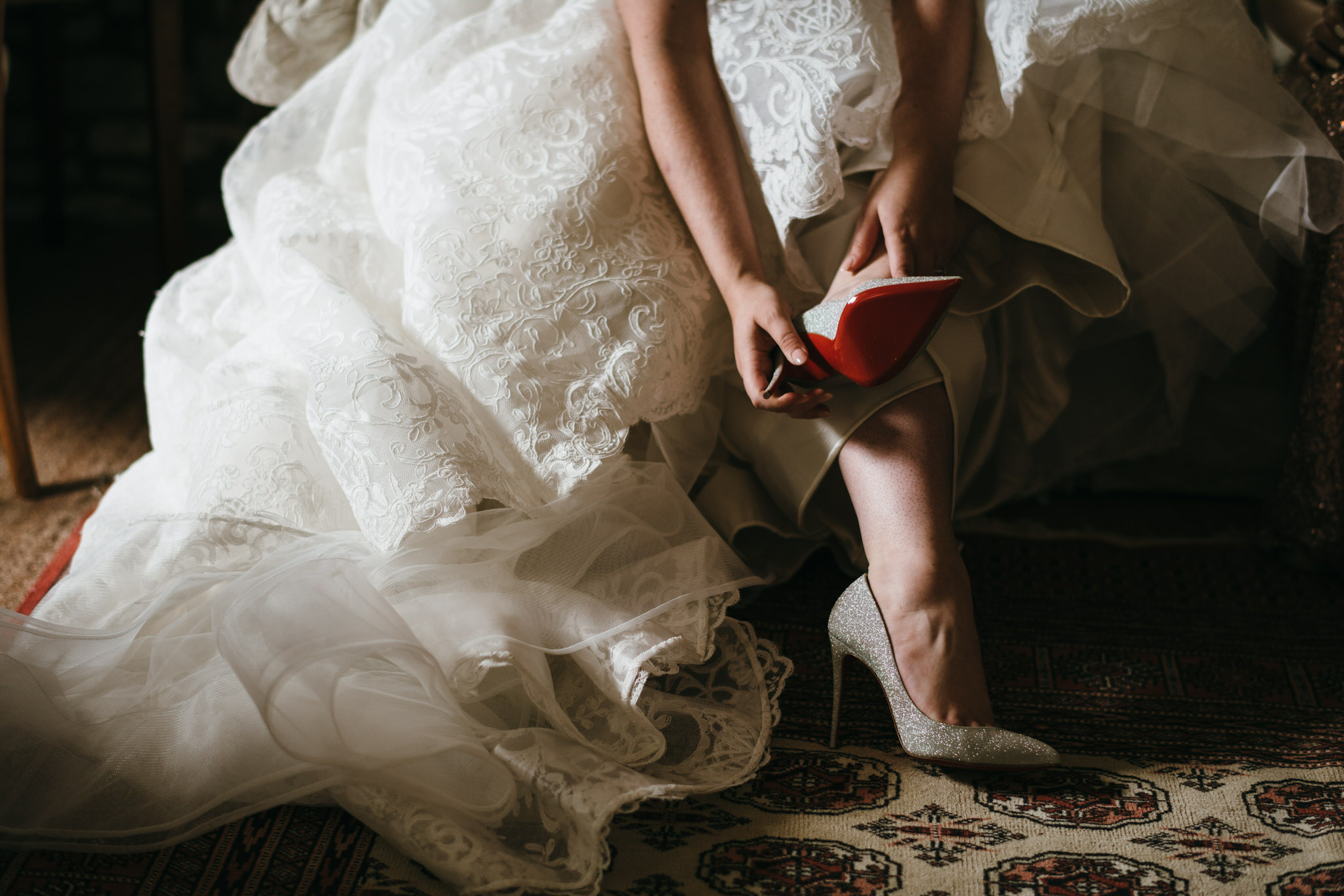 Bride putting her Jimmy Choo shoes on