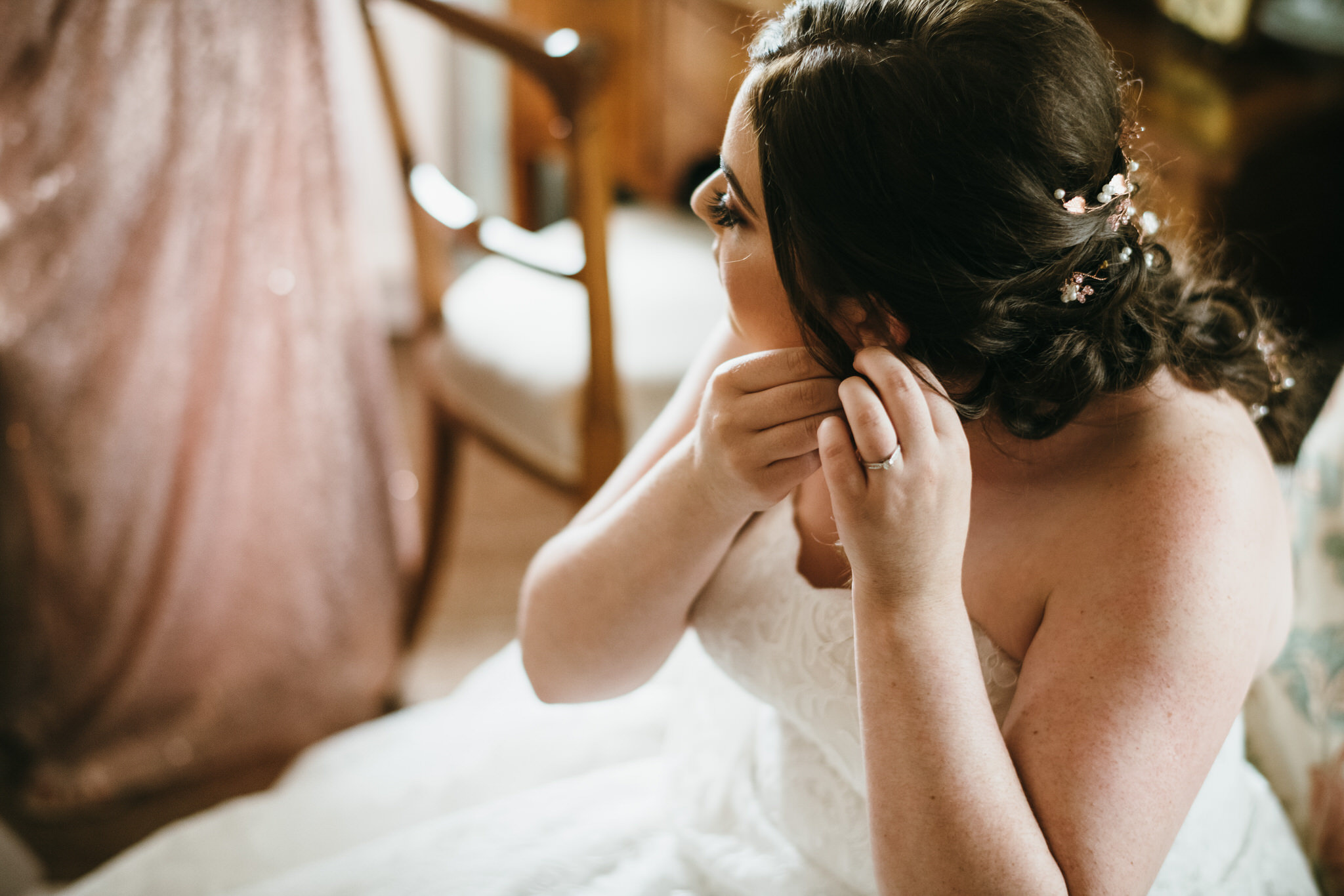 Bride puts earrings on while sat down