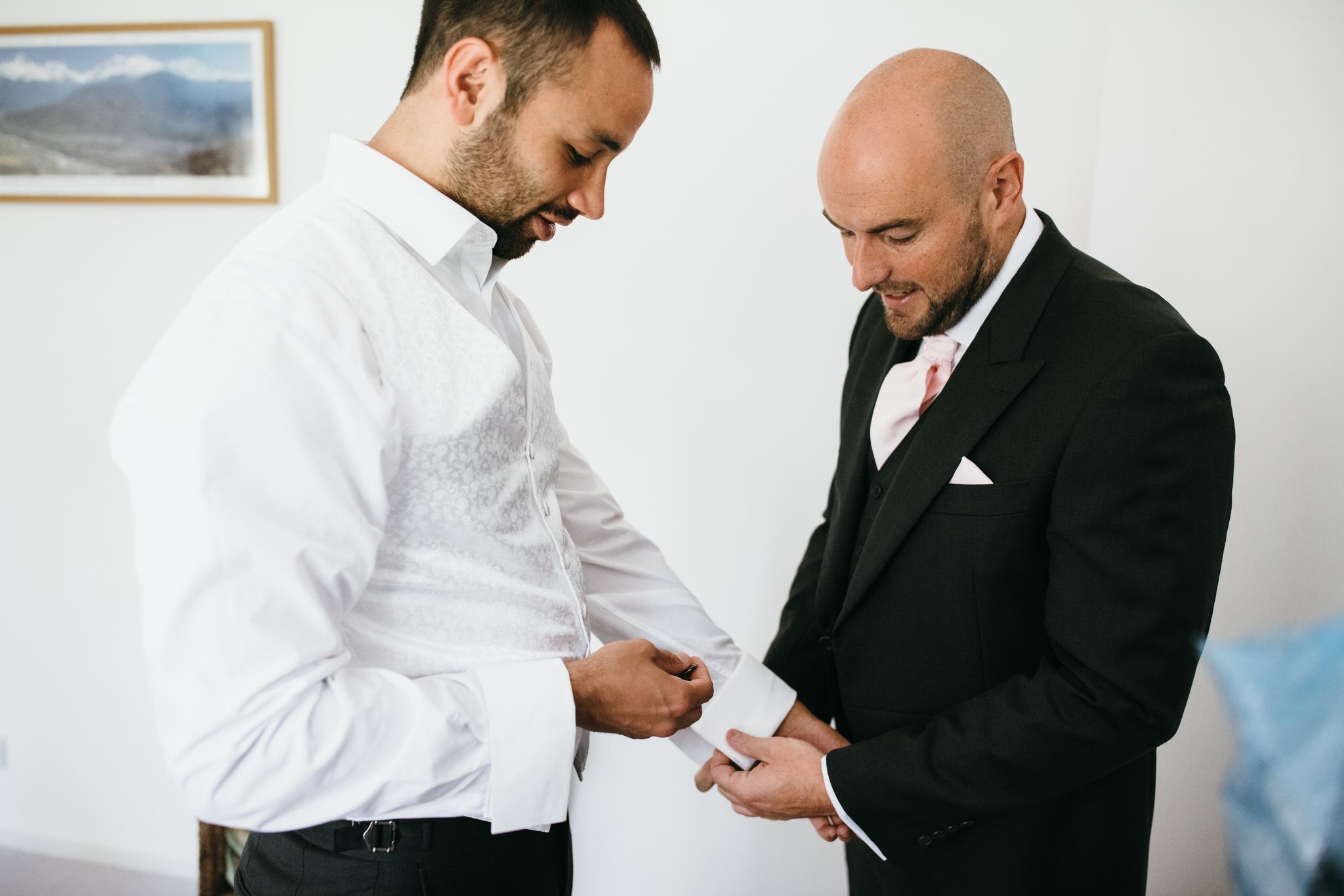 Groom and usher put wedding cufflinks on