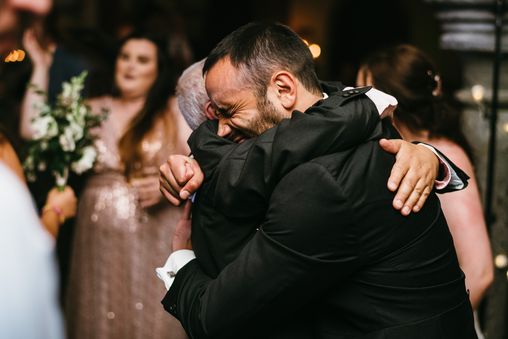Emotional Groom hugging father tight