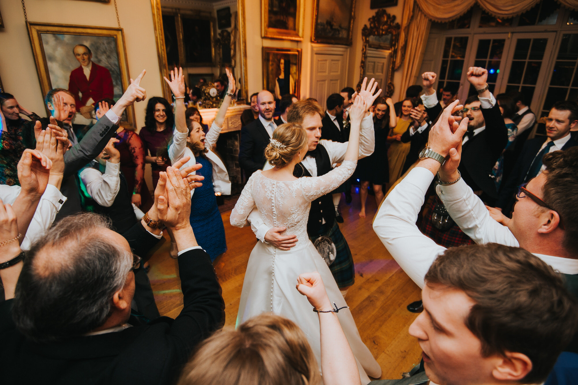 Guests dance around the bride and groom at a maunsel house wedding