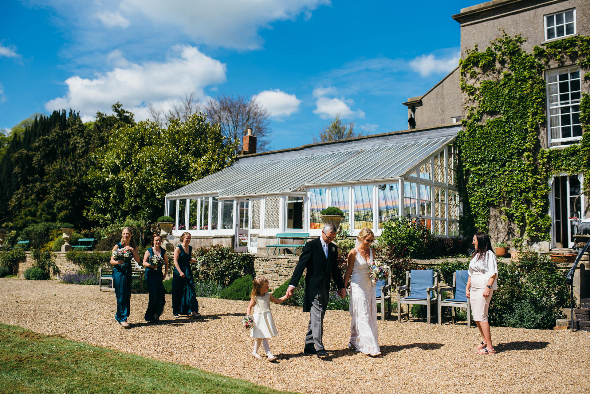 Bridal party walk to church at Pennard House