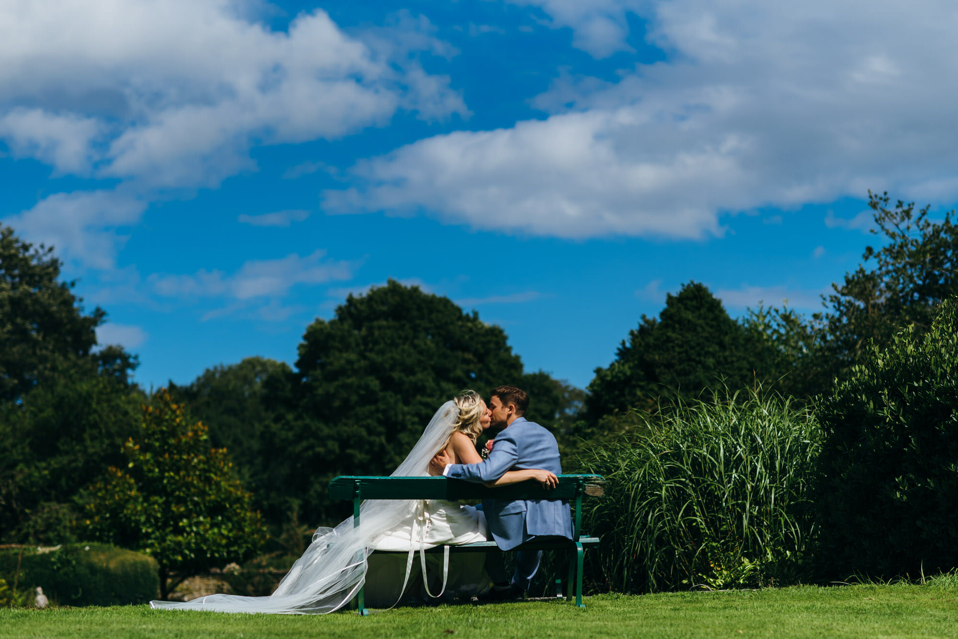 Wedding couple kiss next to pond at Pennard house Somerset