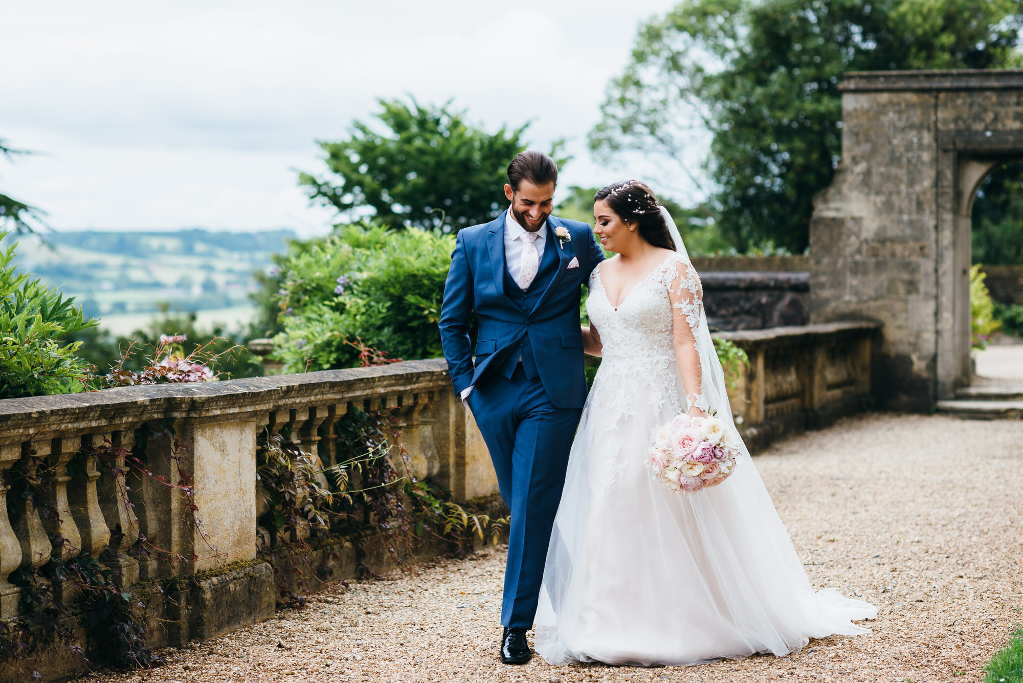 Bride and groom walking along terrace at Coombe lodge wedding venue