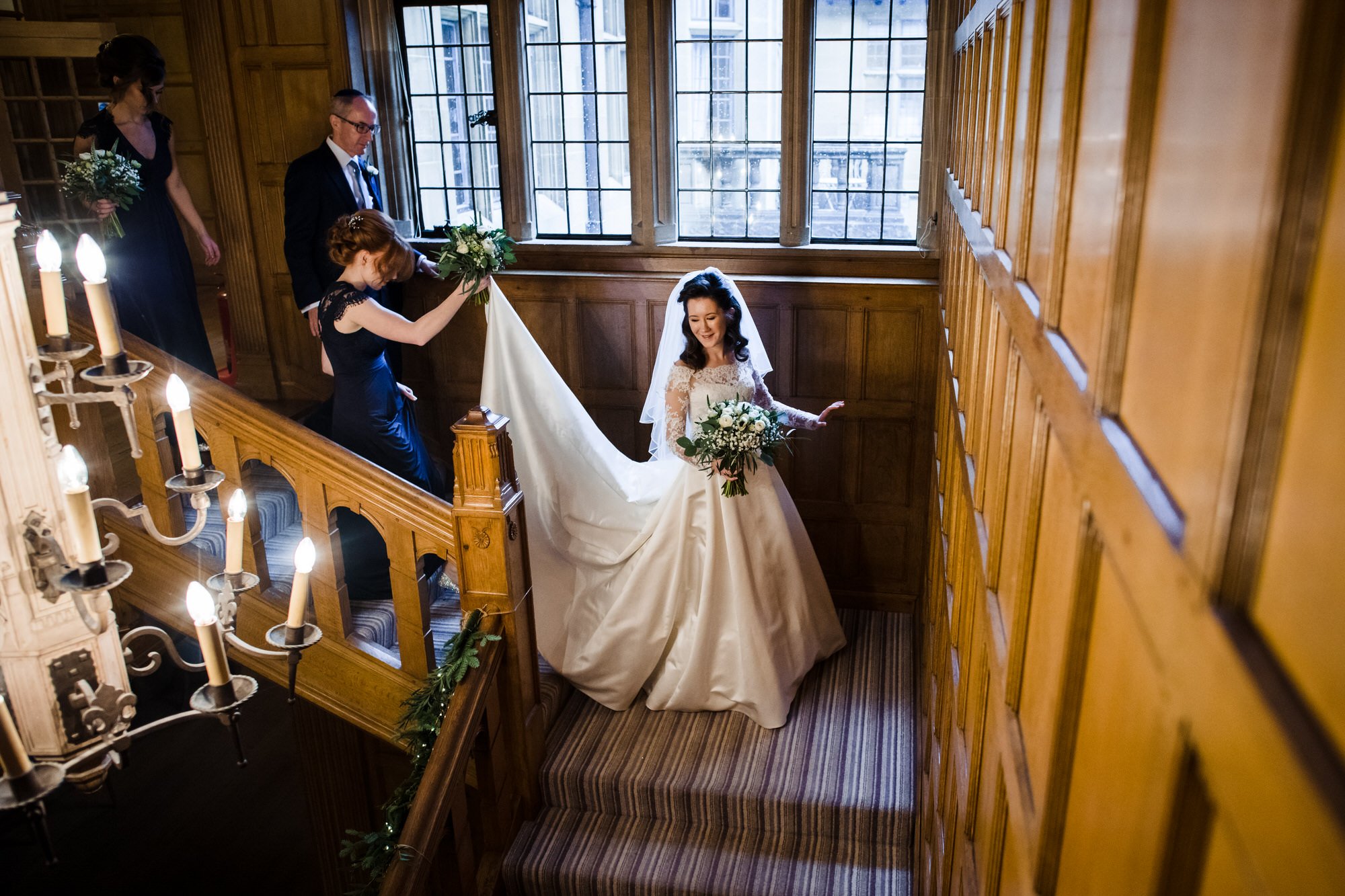Bride walks down stairs at Coombe lodge wedding venue