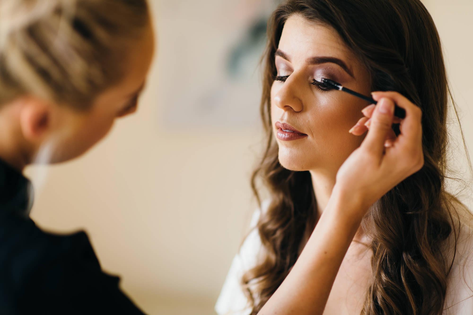 Make up artist working on the brides eye